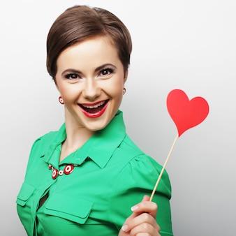 Mujer joven feliz con corazón de papel rojo y listo para la fiesta