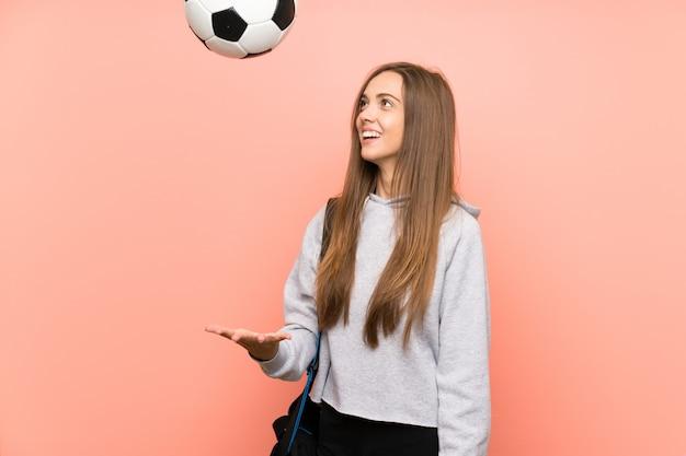 Mujer joven feliz del deporte sobre el fondo rosado aislado que sostiene un balón de fútbol