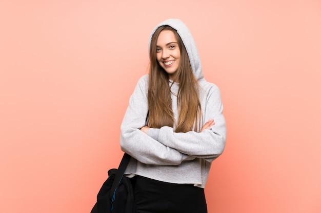 Mujer joven feliz del deporte sobre fondo rosado aislado
