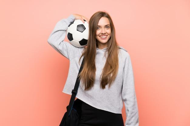 Mujer joven feliz del deporte sobre la pared rosada aislada que sostiene un balón de fútbol