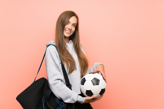 Mujer joven feliz del deporte sobre rosa aislado que sostiene un balón de fútbol