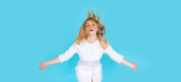 Mujer joven feliz divertida en uniforme blanco