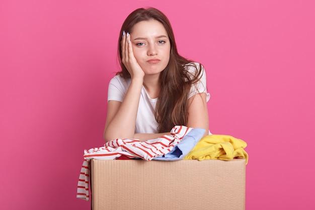 Mujer joven feliz con donación de ropa de pie sobre rosa, empacando ropa reutilizable para personas pobres, hembra mantiene la mano debajo de la barbilla, mirando aburrida a la cámara.