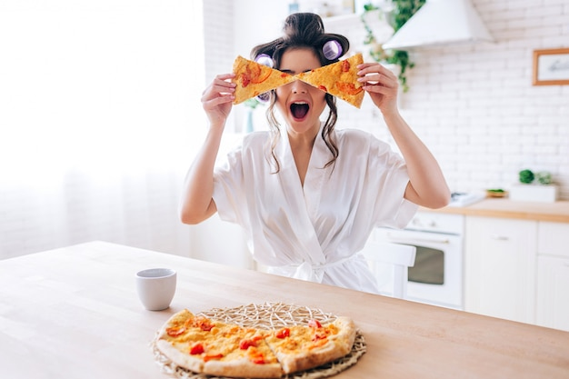 Mujer joven feliz emocionada en cocina plaing con las rebanadas de pizza. cubra los ojos con comida. despreocupada ama de llaves muy juguetona. usa una bata blanca. ama de casa descuidada.