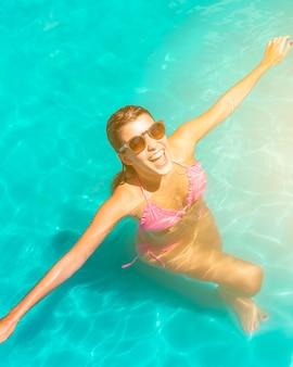 Mujer joven feliz emocionada que se coloca en piscina