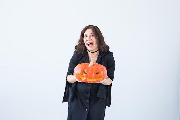 Mujer joven feliz emocionada en traje de halloween que presenta con la calabaza tallada en la sala de luz.