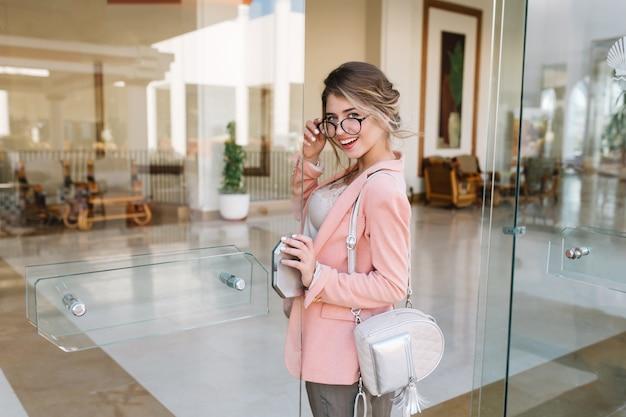 Mujer joven feliz entrando por la puerta de cristal en un hotel moderno, cafetería, centro de negocios. lleva gafas elegantes, chaqueta rosa, pequeña mochila plateada.