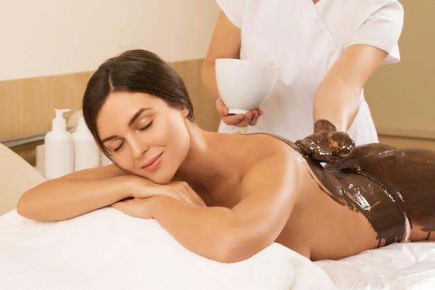 Mujer joven feliz durante una envoltura de chocolate o masaje