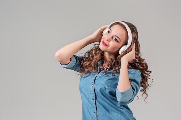 Mujer joven feliz escuchando música con auriculares. retrato aislado en pared gris