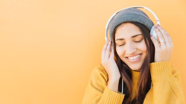 Mujer joven feliz escuchando música en auriculares