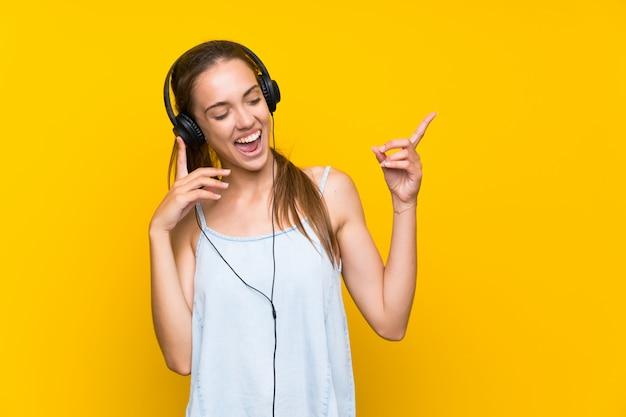 Mujer joven feliz escuchando música sobre la pared amarilla aislada cantando