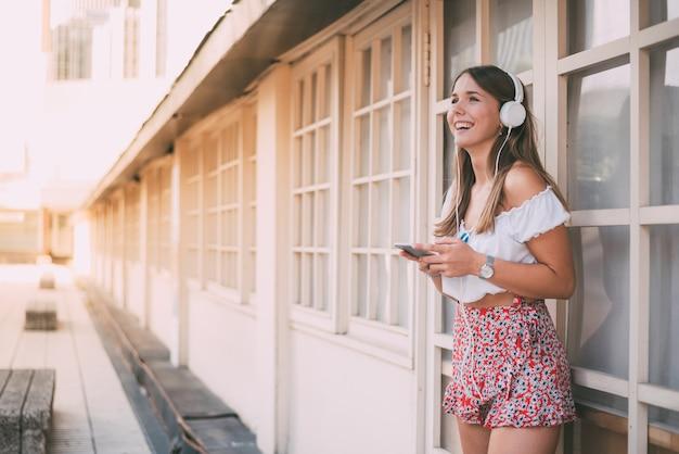 Mujer joven feliz escuchando música en el teléfono móvil