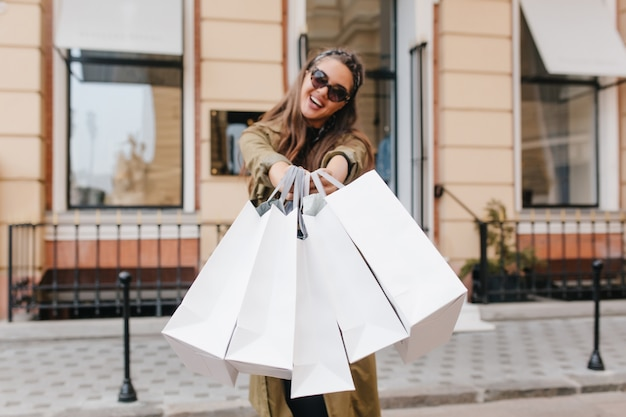 Mujer joven feliz con gafas de sol y abrigo largo sosteniendo paquetes durante la sesión de fotos en la calle