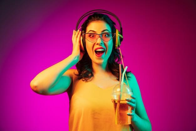 Mujer joven feliz en gafas de sol rojas bebiendo y escuchando música en neón rosa de moda