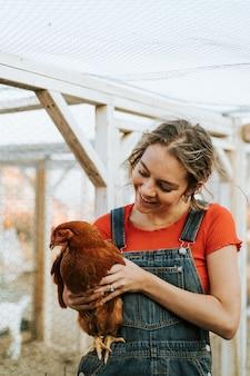 Mujer joven feliz con una gallina marrón
