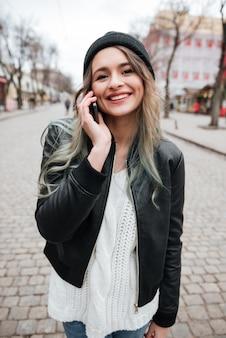 Mujer joven feliz hablando por teléfono móvil.