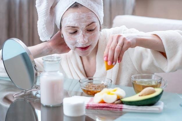 Mujer joven feliz hermosa con la máscara cosmética natural en su cara. cuidado de la piel y tratamientos de spa en casa.