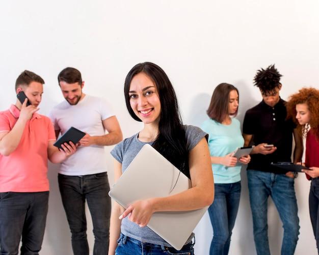 Mujer joven feliz hermosa que mira la cámara que sostiene el ordenador portátil mientras que sus amigos ocupados en usar los artilugios electrónicos