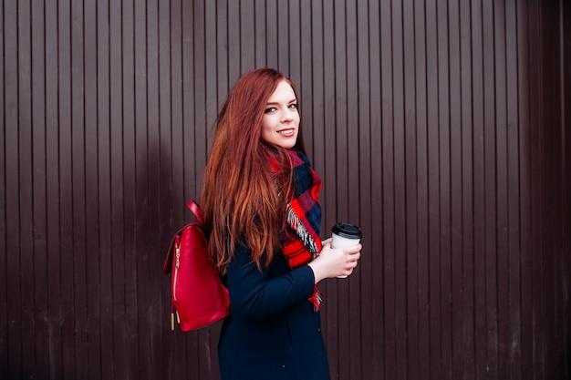 Mujer joven feliz hermosa que sostiene una taza de papel y que bebe el café. mujer alegre con el pelo largo rojo en la calle bebiendo café de la mañana