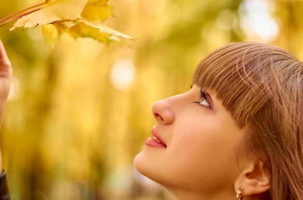 Mujer joven feliz con hojas amarillas.