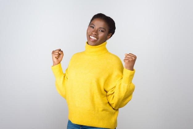 Mujer joven feliz levantando puños
