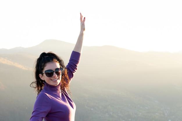 Mujer joven feliz con la mano levantada disfrutando de la cálida tarde del atardecer en las montañas de verano.