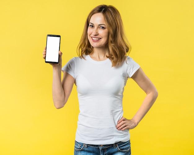 Mujer joven feliz con las manos en su cadera que muestra el teléfono móvil con la pantalla de visualización blanca