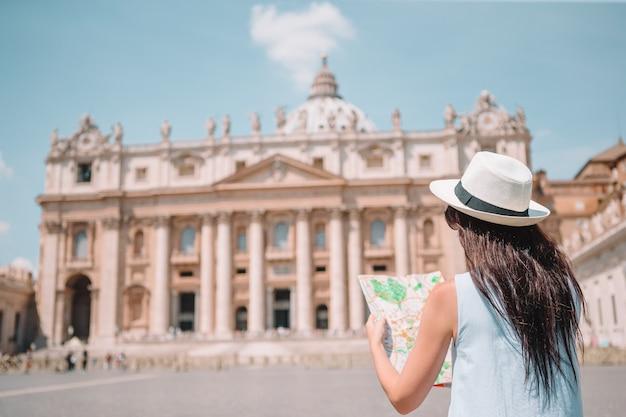 Mujer joven feliz con el mapa de la ciudad en la ciudad del vaticano y la iglesia de la basílica de san pedro, roma, italia.