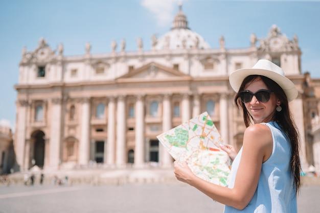 Mujer joven feliz con el mapa de la ciudad en la ciudad del vaticano y la iglesia de la basílica de san pedro