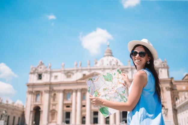 Mujer joven feliz con el mapa de la ciudad en la ciudad del vaticano y san, la basílica de peter, iglesia, roma, italia,