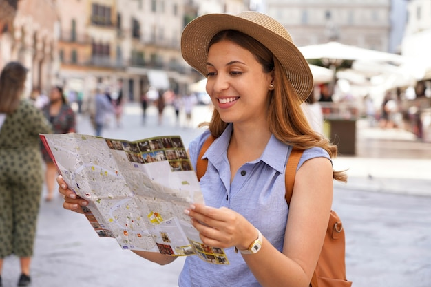 Mujer joven feliz con un mapa de la ciudad, sombrero de paja y mochila viajando