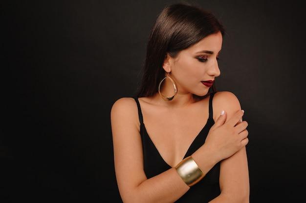 Mujer joven feliz con maquillaje brillante y joyas doradas en vestido negro posando