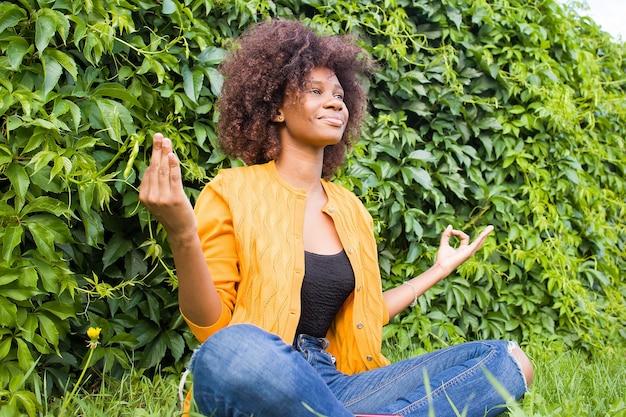 Una mujer joven y feliz medita sobre la hierba