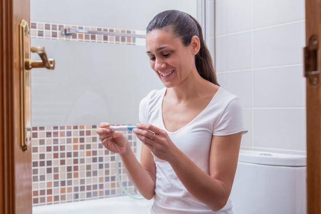 Mujer joven, feliz mirando la prueba de embarazo en el baño de su casa
