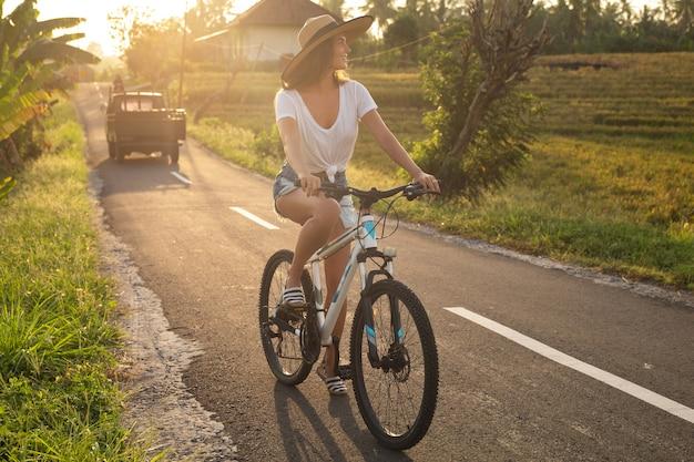Mujer joven feliz está montando bicicleta por estrecho camino rural