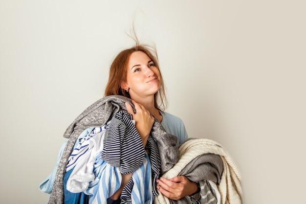 Mujer joven feliz con montón de ropa de temporada desordenada sobre fondo blanco.