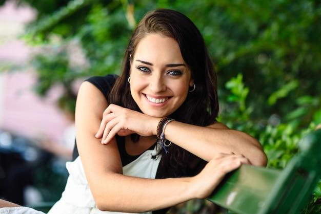 Mujer joven feliz con los ojos azules que miran la cámara.