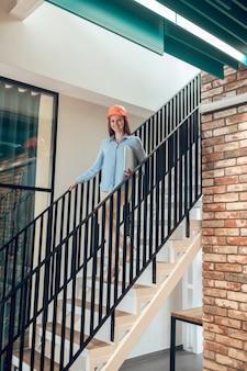 Mujer joven feliz en pasos en edificio nuevo