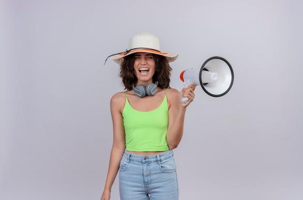 Una mujer joven feliz con el pelo corto en la parte superior de la cosecha verde en auriculares con sombrero para el sol sonriendo y sosteniendo el megáfono sobre un fondo blanco.