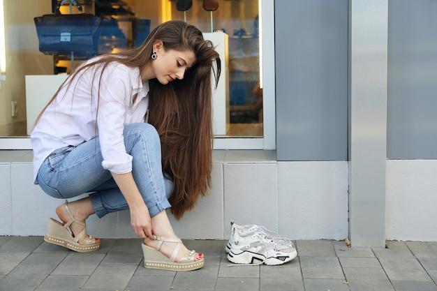 Mujer joven feliz con el pelo largo endereza la hebilla de los zapatos junto a la vitrina