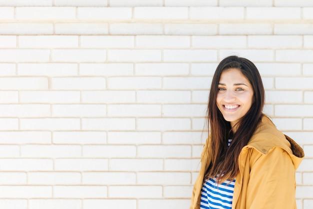 Mujer joven feliz de pie contra la pared de ladrillo