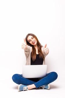 Mujer joven feliz con un portátil sobre un blanco