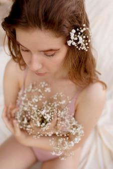 Mujer joven feliz posando con flores
