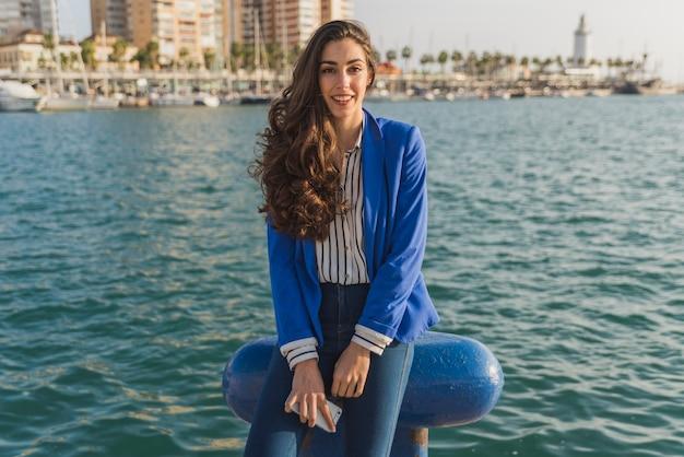 Mujer joven feliz posando con el mar de fondo