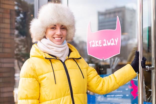 Mujer joven feliz en la puerta del restaurante en un día frío de invierno, rotulación, comida para llevar.