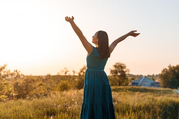 La mujer joven feliz en la puesta del sol del verano en el campo levanta sus manos al cielo.