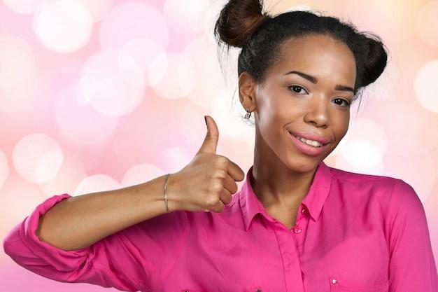 Mujer joven feliz con los pulgares para arriba