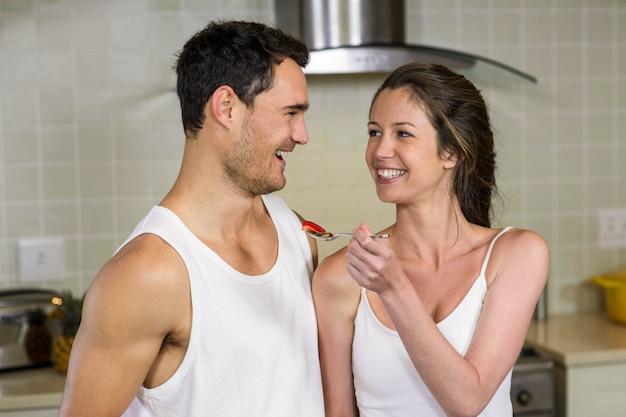 Mujer joven feliz que alimenta el desayuno a su hombre en cocina
