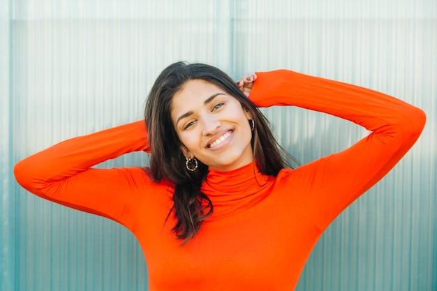Mujer joven feliz que se coloca delante de fondo metálico de la textura
