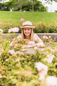 Mujer joven feliz que se coloca en parque cerca de las flores